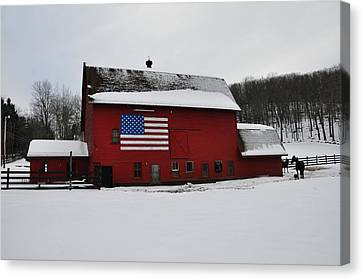 Red Barn With Flag In The Snow Canvas Print by Bill Cannon