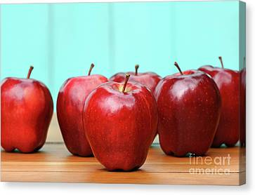 Red Delicious Apples On Old School Desk Canvas Print by Sandra Cunningham
