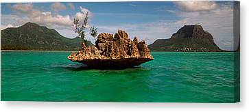Rock In Indian Ocean With Mountain Canvas Print by Panoramic Images