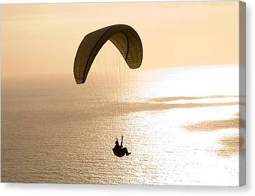 Silhouette Of A Paraglider Flying Canvas Print by Panoramic Images