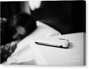 Smartphone On Bedside Table Of Early Twenties Woman In Bed In A Bedroom Canvas Print by Joe Fox