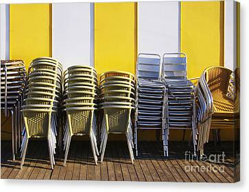 Stacks Of Chairs And Tables Canvas Print by Carlos Caetano