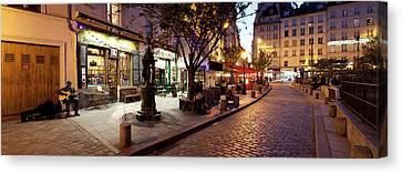 Stores At Dusk, Paris, Ile-de-france Canvas Print by Panoramic Images