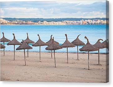 Straw Umbrellas On Empty Beach Canvas Print by Christina Rahm
