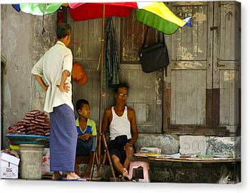 Street Seller Sitting In The Shade Under An Umbrella Yangon Myanmar Canvas Print by Ralph A  Ledergerber-Photography