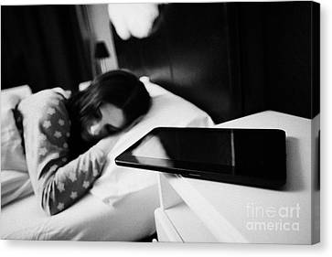 Tablet Computer On Bedside Table Of Early Twenties Woman In Bed In A Bedroom Canvas Print by Joe Fox