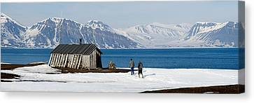 Two Hikers Standing On The Beach Canvas Print by Panoramic Images