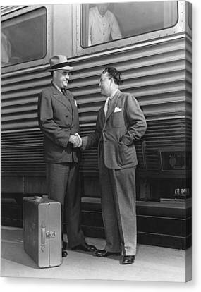 Two Men Shaking Hands At Train Canvas Print by Underwood Archives