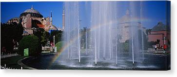 Water Fountain With A Rainbow In Front Canvas Print by Panoramic Images