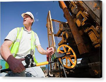 Workman Measuring Borehole Canvas Print by Ashley Cooper