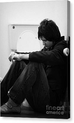 Young Dark Haired Teenage Man Sitting On The Floor Of The Bathroom With Back Against The Wall In The Canvas Print by Joe Fox