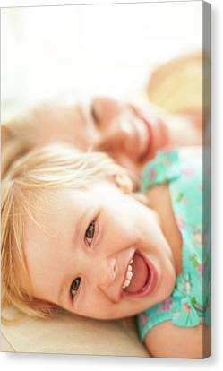 Young Girl Lying Down Laughing Canvas Print by Ian Hooton