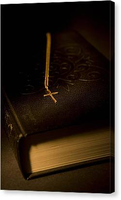 Gold Cross Pendant Resting On A Book Canvas Print by Philippe Widling