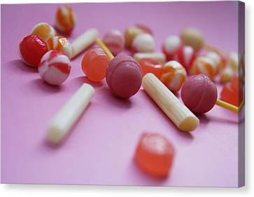 Unwrapped Hard Candies On Pink Paper Canvas Print by Asia Images