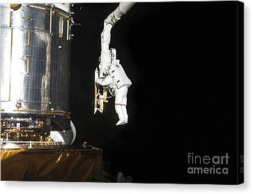 Astronaut Working On The Hubble Space Canvas Print by Stocktrek Images