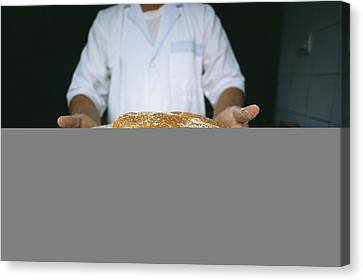 A Baker Shows His Fresh Loaves Canvas Print by Heather Perry