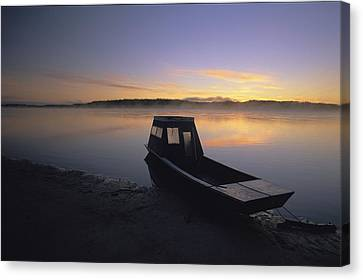 A Boat Sits On The Calm Yukon River Canvas Print by Michael Melford