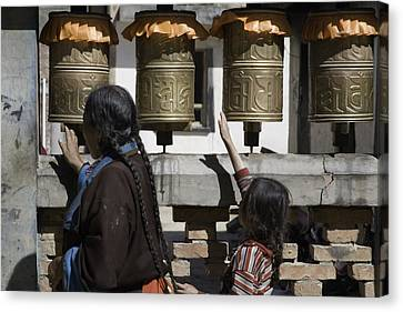 A Buddhist Woman And Child Spin Brass Canvas Print by David Evans
