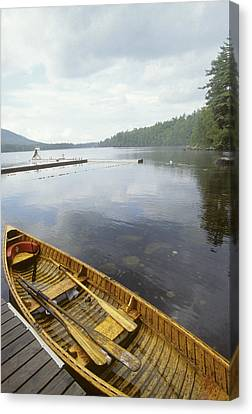 A Canoe Floats Next To A Dock Canvas Print by Skip Brown