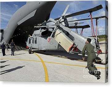 A Helicopter Is Loaded Onto A C-17 Canvas Print by Stocktrek Images