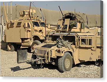 A M1114 Humvee Sits Parked In Front Canvas Print by Stocktrek Images