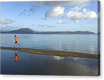 A Man Running On A Beach Is Reflected Canvas Print by Bill Hatcher