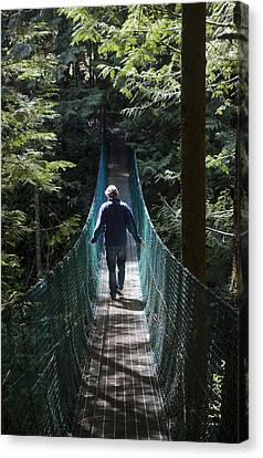 A Man Walks Across A Suspension Bridge Canvas Print by Taylor S. Kennedy