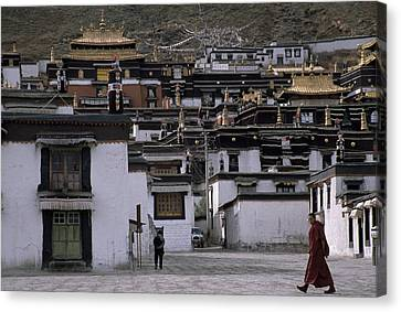 A Monk Walks Past A Small Village Canvas Print by Jimmy Chin