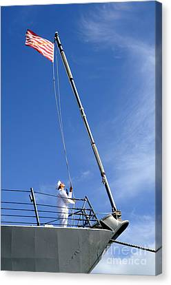 A Sailor Lowers The U.s. Navy Jack Canvas Print by Stocktrek Images