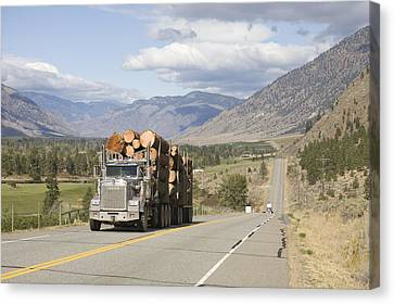 A Truck Carries Logs Down The Highway Canvas Print by Taylor S. Kennedy