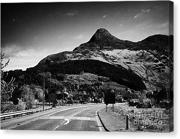 A82 Road Into Glencoe With The Pap Of Glencoe In The Highland Of Scotland Uk Canvas Print by Joe Fox