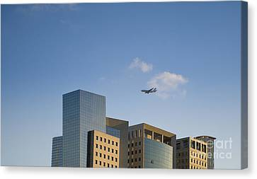 Airplane Flying Over Office Buildings Canvas Print by Noam Armonn