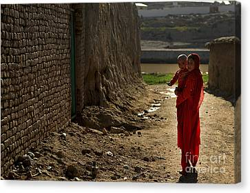 An Afghan Girl Carries Her Little Canvas Print by Stocktrek Images