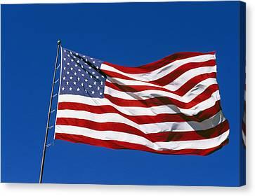 An American Flag Flies In A Clear Blue Canvas Print by Stephen Alvarez
