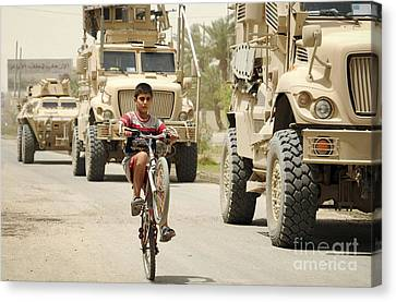 An Iraqi Boy Rides His Bike Past A U.s Canvas Print by Stocktrek Images