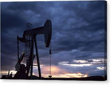 An Oil Rig Silhouetted At Sunset Canvas Print by Joel Sartore