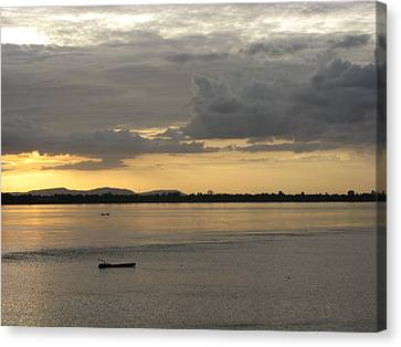 Boat On River At Sunset Canvas Print by Nawarat Namphon