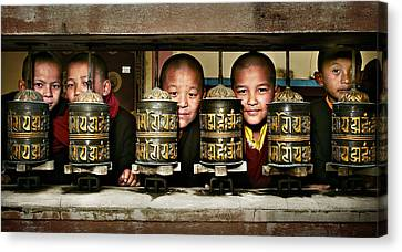 Buddhist Monks In Red Robes Look Out Of The Prayer Wheels With M Canvas Print by Max Drukpa