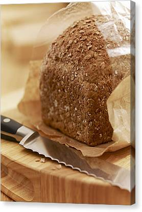 Close Up Of Knife And Loaf Of Bread In Wrapper Canvas Print by Adam Gault
