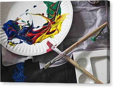 Heaps Of Acrylic Paint On A Paper Plate And Paintbrushes Canvas Print by Tobias Titz