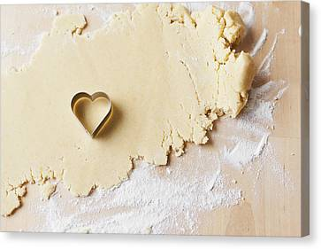 Heart Shaped Cookie Cutter On Dough Canvas Print by Cultura/Nils Hendrik Mueller