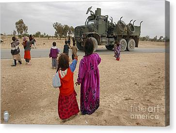 Iraqi Children Wave To An American Canvas Print by Stocktrek Images