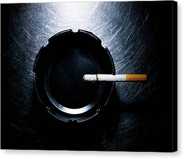Lit Cigarette And Ashtray On Stainless Steel. Canvas Print by Ballyscanlon