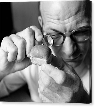 Man Looking At Miniture Loaf Of Bread Through Magnifying Glass Canvas Print by Hulton Archive