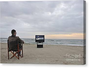 Man Watching Tv On Beach At Sunset Canvas Print by Sami Sarkis