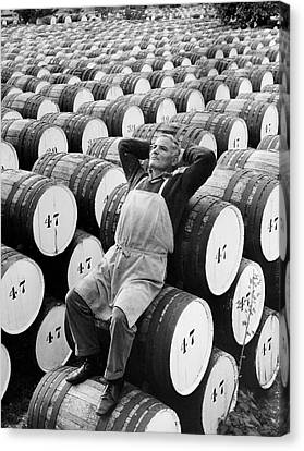 Mature Man Relaxing On Barrels (b&w) Canvas Print by Hulton Archive