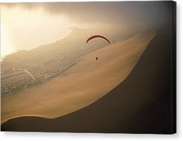 Ocean Gusts Keep A Paraglider Aloft Canvas Print by Joel Sartore