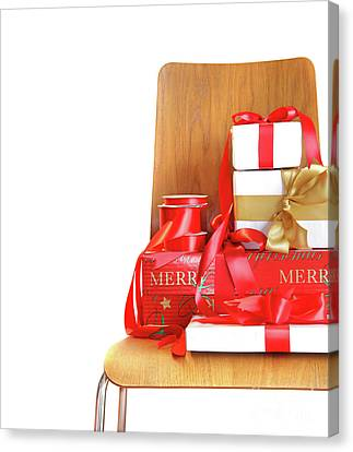Pile Of Gifts On Wooden Chair Against White Canvas Print by Sandra Cunningham
