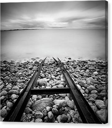 Railroad Tracks Into Water Canvas Print by Peter Levi