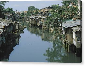Ramshackle Houses Line A Canal Canvas Print by Tim Laman